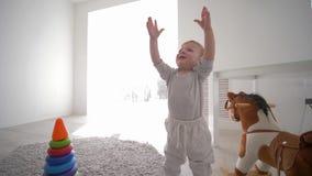 Le garçon de sourire doux d'enfant en bas âge joue dans la chambre de jeu avec des jouets à la maison dans la lumière naturelle banque de vidéos