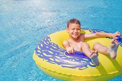 Le garçon de sourire gai a plaisir à flotter sur l'anneau gonflable dans la piscine en parc d'aqua photos stock