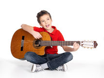 Le garçon de sourire joue la guitare acoustique Photo stock
