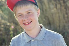 Le garçon de sourire mignon avec des taches de rousseur utilise le chapeau images libres de droits