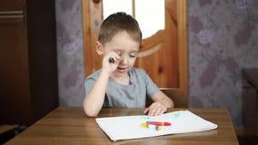 Le garçon de sourire mignon s'assied à la table à la maison et dessine sur le papier avec les crayons colorés lumineux Éducation  clips vidéos