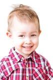 Le garçon de sourire regarde avec un strabisme Image stock