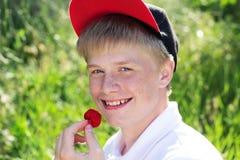 Le garçon de sourire utilise le chapeau rouge mangeant la fraise photo libre de droits