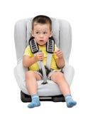 Le garçon de trois ans s'assied dans une chaise du ` s d'enfants d'automobile Image libre de droits