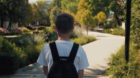 Le garçon descend la rue avec un sac à dos Un enfant voyage le monde banque de vidéos
