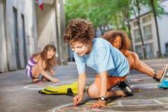 Le garçon dessine avec des amis dans la craie sur l'asphalte Photographie stock
