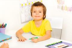 Le garçon dessine avec le stylo pendant se reposer à la table Photographie stock