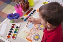 Le garçon dessine des peintures images libres de droits