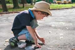 Le garçon dessine sur la route avec la craie Images libres de droits