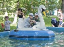 Le garçon deux gai contrôlent le cygne de bateau Image stock