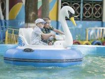 Le garçon deux gai contrôlent le cygne de bateau Photographie stock