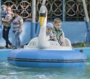 Le garçon deux gai contrôlent le cygne de bateau Photographie stock libre de droits