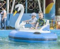 Le garçon deux gai contrôlent le cygne de bateau Photo stock