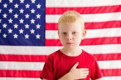 Le garçon devant le drapeau américain avec remettent le coeur image libre de droits