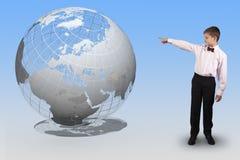 Le garçon dirige un doigt à un globe translucide Photographie stock libre de droits