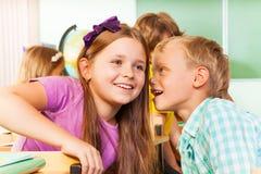 Le garçon dit le secret à l'autre belle fille à l'école Photo libre de droits
