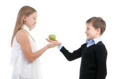 Le garçon donne à la fille une pomme Images stock