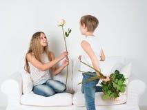 Le garçon donne à une fille des fleurs Images libres de droits