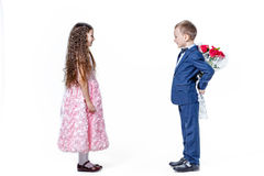 Le garçon donne à une fille des fleurs le jour du St valentine photographie stock