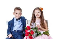 Le garçon donne à une fille des fleurs le jour du St valentine Images stock