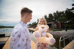 Le garçon donne à une fille un ours de nounours Photo libre de droits