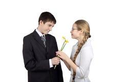 Le garçon donne des fleurs à l'amie Images stock