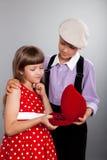 Le garçon donne des petits programmes à la fille Rétro type Image libre de droits