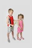 Le garçon donne le bouquet de fille des marguerites sur le gris Photos stock