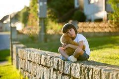 Le garçon doux, jouant avec le nounours concernent un petit chemin rural sur les soleils photos stock