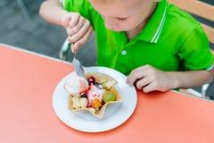 Le garçon drôle mignon heureux mange la crème glacée en café Image libre de droits