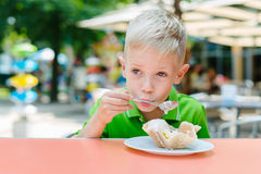 Le garçon drôle mignon heureux mange la crème glacée en café Photos libres de droits