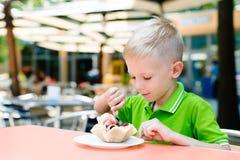 Le garçon drôle mignon heureux mange la crème glacée en café Photographie stock libre de droits