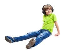 Le garçon drôle s'asseyant sur le plancher blanc Photographie stock libre de droits