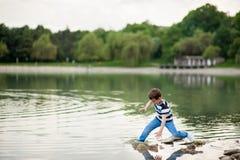 Le garçon, drôle, vilain, chute, trébuchement, a mouillé, lac, l'eau, danger, perdent l'équilibre, enfant Image libre de droits