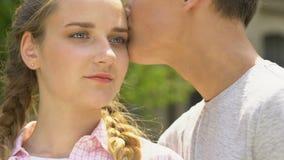 Le garçon embrasse la fille, concept des soins de la peau dans l'adolescence, aucune acné, confiance en soi banque de vidéos