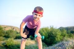 Le garçon en bonne santé se penche en avant tout en soulevant des poids Photographie stock