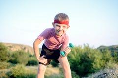 Le garçon en bonne santé se penche en avant tout en soulevant des poids Photos libres de droits