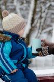 Le garçon en hiver vêtx prendre une tasse de mains femelles sur un fond des arbres neigeux Photos stock
