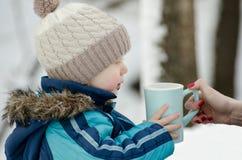 Le garçon en hiver vêtx prendre une tasse de mains femelles sur un fond des arbres neigeux Images stock