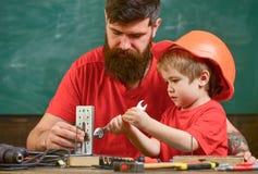 Le garçon, enfant dans le casque de protection fait à la main, réparant, fait des métiers avec le papa Père avec la barbe et peti photo stock