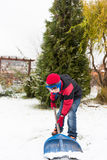 Le garçon enlève la pelle à neige pendant l'hiver Photos stock
