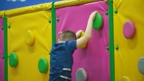 Le garçon escalade le mur banque de vidéos