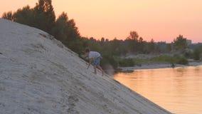 Le garçon escalade une montagne arénacée au coucher du soleil Reste actif de l'enfant banque de vidéos
