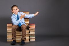 Le garçon est chef s'asseyant sur un trône des livres Photos libres de droits