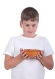 Le garçon est des regards appétissants à une plaque Photographie stock