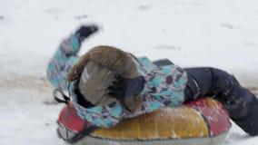 Le garçon est descendu la colline sur le tube de neige clips vidéos