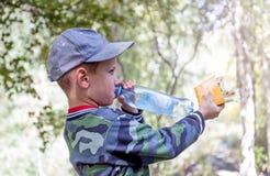 Le garçon est eau potable  Photos libres de droits