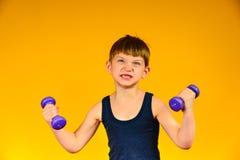Le garçon est engagé dans le bodybuilding, sports à un jeune âge, l'haltérophilie de l'enfant image stock
