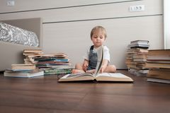 Le garçon est entouré par des livres images stock