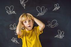 Le garçon est mordu par des moustiques sur un fond foncé Sur le tableau noir avec les moustiques peints par craie photographie stock libre de droits